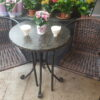 table and chairs with teacups and flowers on top